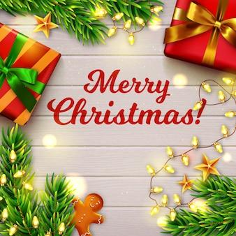 Vrolijk kerstfeest! houten tafel versierd met geschenken, kerstboomtakken, peperkoekmannetje en lichtslinger. bovenaanzicht.