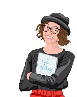 Vrolijk meisje in zwart t-shirt, rode jurk, bril en zwarte fedora met een notitieboekje met terug naar school-inscriptie