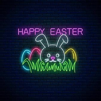 Vrolijk pasen gloeiend uithangbord met konijntje en gekleurde eieren op gras in neonstijl op donkere bakstenen muurachtergrond.