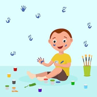 Vrolijk zit de zitting van weinig kindjongen op vloer en het spelen met de kleurrijke illustratie van vingerverven. hij tekent met zijn handen op kunstles, kleuterschool of thuis.
