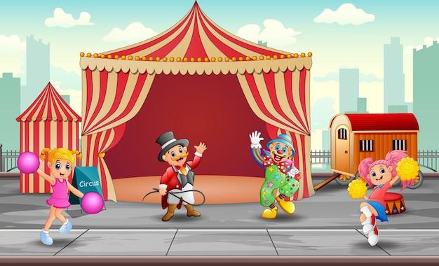 Vrolijke clown cheerleaders en trainer in de circustent