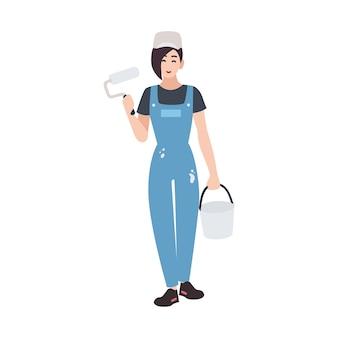 Vrolijke huisschilder of decorateur die tuinbroek draagt en verfrol en emmer vasthoudt