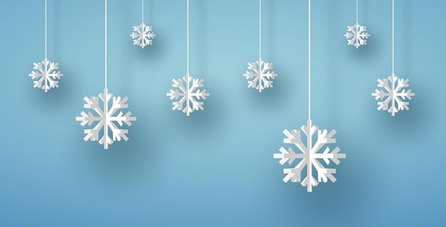Vrolijke kerstkaart met witte origamisneeuwvlok of ijskristal op blauwe achtergrond