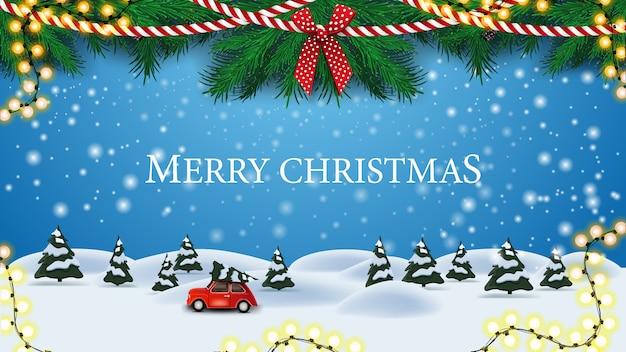 Vrolijke kerstmis, blauwe wenskaart met kerstboomtakken, slingers en cartoon winterlandschap met rode vintage auto met kerstboom