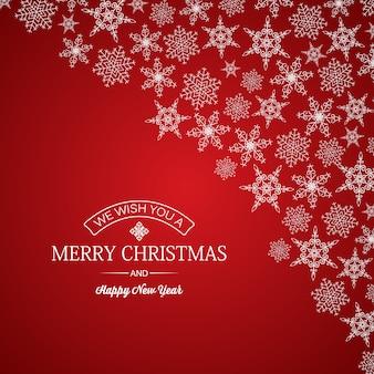 Vrolijke kerstmis en nieuwjaarskaart groet inscriptie en sneeuwvlokken van verschillende vormen op rood