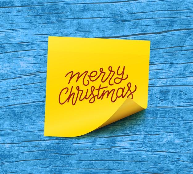Vrolijke kerstmistekst op geel kleverig notadocument