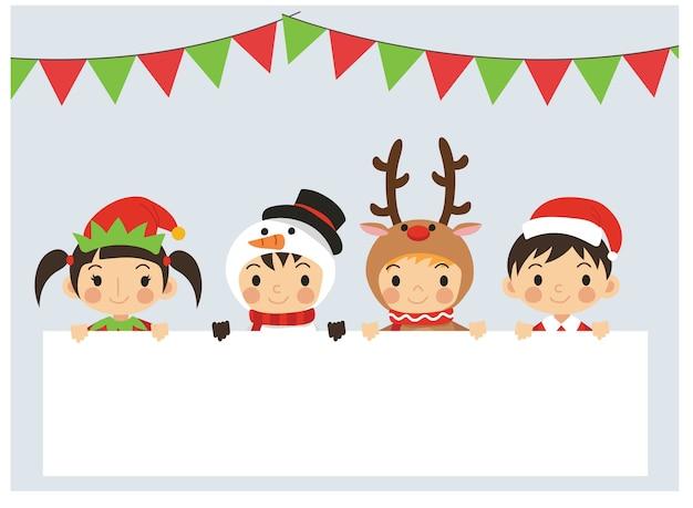 Vrolijke kinderen in verschillende kerstkostuums staan achter een leeg tekstvak. schattige kleine kerstkinderen.