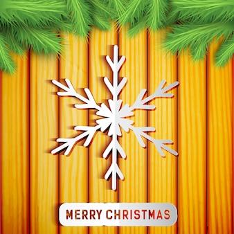 Vrolijke lichte kerstkaart met papieren sneeuwvlok groene fir takken op hout