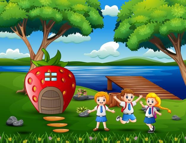 Vrolijke schoolkinderen in de buurt van het aardbeienhuis