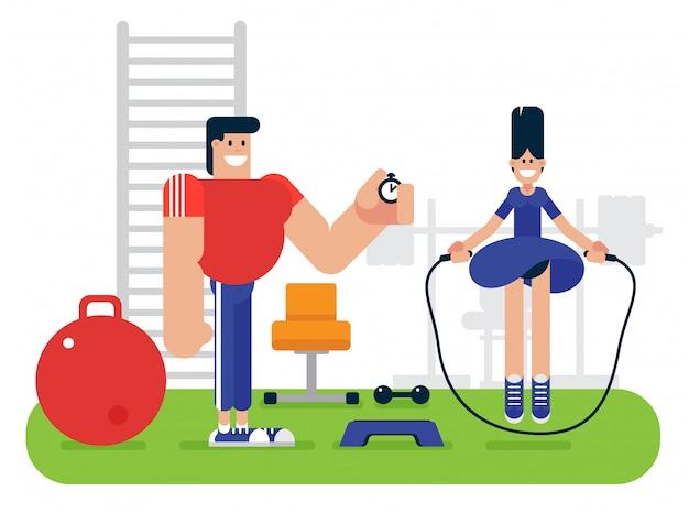 Vrolijke vrouw die met kabel dichtbij geschiktheidsinstructeur springen met tijdopnemer tijdens training in gymnastiek
