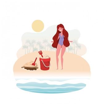 Vrouw aan de oever van het strand met zand emmer