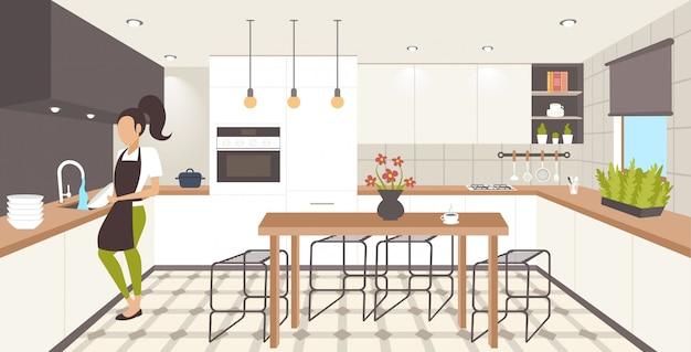 Vrouw afwas gerechten huisvrouw afvegen platen afwassen concept meisje in schort huishoudelijk werk doen moderne keuken interieur horizontale volledige lengte