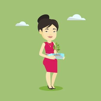 Vrouw bedrijf plant groeit in plastic fles.