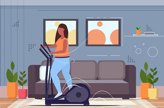 Vrouw bezig met elliptische trainer overgewicht meisje doet spinnen oefeningen cardio training workout gewichtsverlies concept woonkamer interieur volledige lengte horizontaal