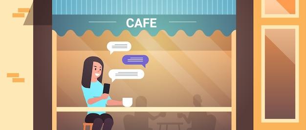 Vrouw bezoeker zittend aan tafel met behulp van chatten mobiele app op smartphone sociaal netwerk chat bubble communicatie