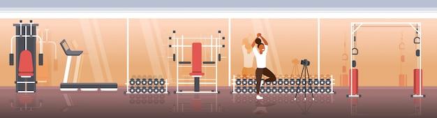 Vrouw blogger doet yoga oefeningen sportvrouw opname online video met camera op statief gezonde levensstijl live streaming blogging concept moderne sportschool interieur horizontaal volledige lengte