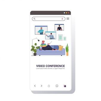 Vrouw chatten met mix race vrienden tijdens video-oproep mensen met online conferentie vergadering communicatieconcept woonkamer interieur smartphone scherm illustratie