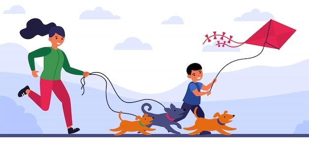 Vrouw die achter honden loopt, en haar zoon na vlieger