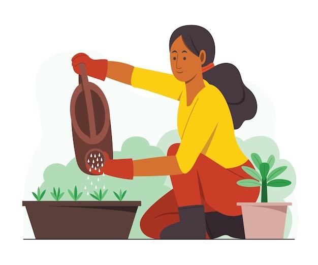 Vrouw die de planten in de tuin water geeft