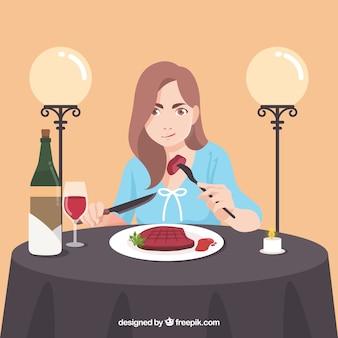 Vrouw die een biefstuk in een elegant restaurant eet