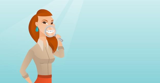 Vrouw die haar tanden met meer magnifier onderzoekt.