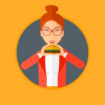 Vrouw die hamburger eet.