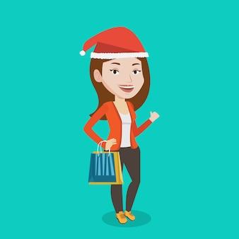 Vrouw die in santahoed voor kerstmisgiften winkelt.