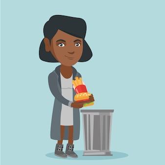 Vrouw die junk food in de vuilnisbak gooit.