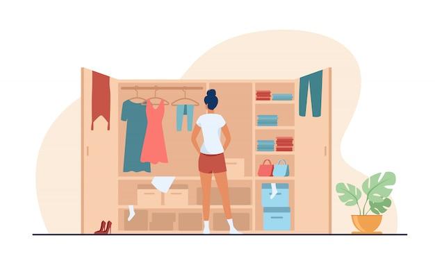 Vrouw die kleding kiezen van garderobe vlakke illustratie