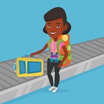 Vrouw die koffer op bagagetransportband opnemen