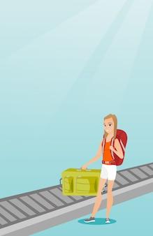 Vrouw die koffer van transportband opnemen.