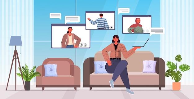 Vrouw die met de vrienden van het mengelingsras babbelen tijdens videogespreksmensen die online communicatie van de conferentievergadering het concept woonkamer binnenlandse horizontale volledige lengteillustratie hebben