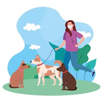 Vrouw die met huisdierenhonden openlucht lopen, dragend medisch masker, tegen coronavirus covid 19