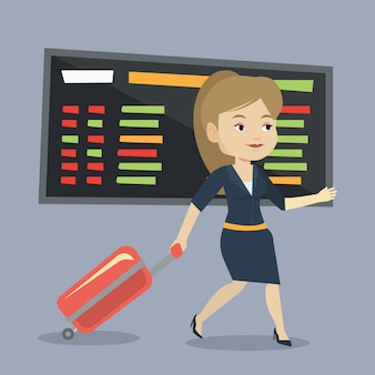 Vrouw die met koffer bij de luchthaven loopt.