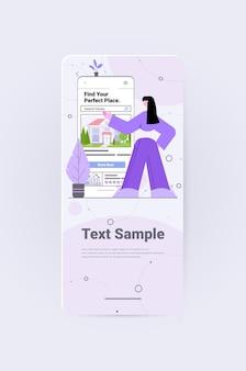 Vrouw die mobiele app gebruikt om huizen te zoeken voor het huren of kopen van online vastgoedbeheerconcept verticale volledige kopieerruimte