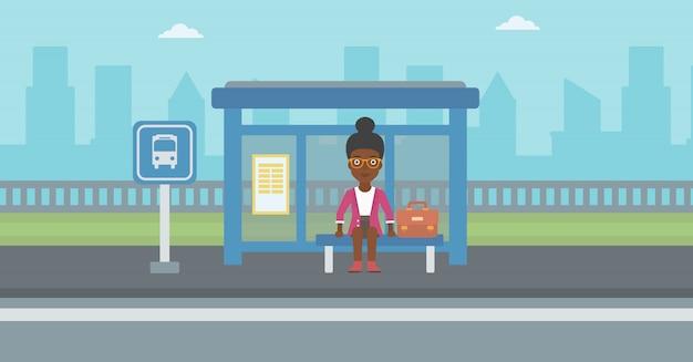 Vrouw die op bus bij de bushalte wacht.