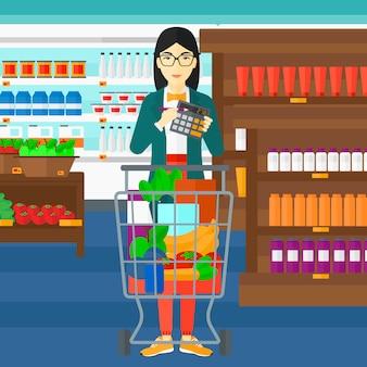 Vrouw die op calculator in de supermarkt telt