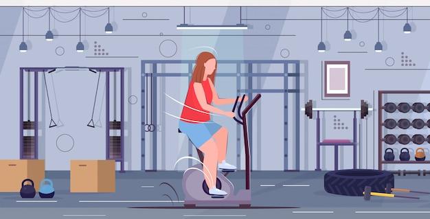 Vrouw die stationair fiets te zwaar meisje doet die het spinnen oefeningen sportactiviteit cardiotraining training het concept van het gewichtsverlies moderne gymnastiekstudio binnenlandse volledige lengte horizontaal doet