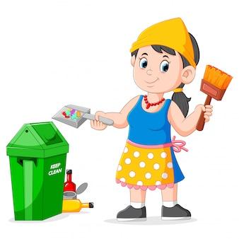 Vrouw die vuilnis schoonmaakt en borstel aan vuilnisbak houdt