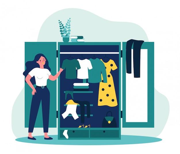 Vrouw die zich dichtbij geopende kast bevindt en kleding bekijkt