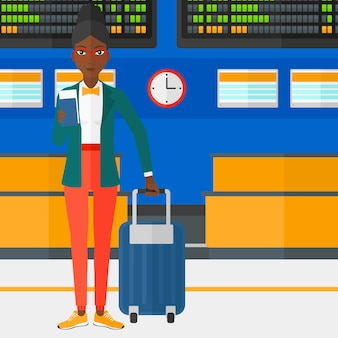 Vrouw die zich met koffer bevindt en kaartje houdt