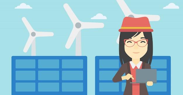 Vrouw die zonnepanelen en windturbines controleert.
