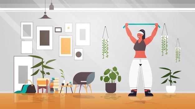 Vrouw doen oefeningen met weerstand band thuis meisje met training cardio fitness training gezonde levensstijl sport concept woonkamer interieur volledige lengte illustratie