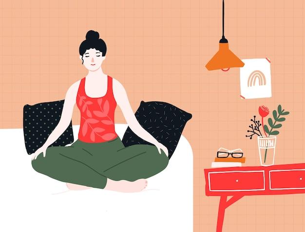 Vrouw doet yoga en meditatie in bed. mindfulnessoefening in lotushouding thuis. gezellige kamer interieur met kussens, nachtkastje, poster en lamp. rust en ontspanning vectorillustratie.