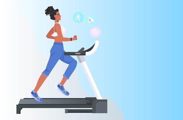 Vrouw draait op loopband afrikaans amerikaans meisje doet fitness oefeningen gezonde levensstijl concept opleiden