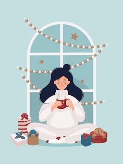 Vrouw drinken van een kopje cacao zitten in de buurt van de kerstcadeaus