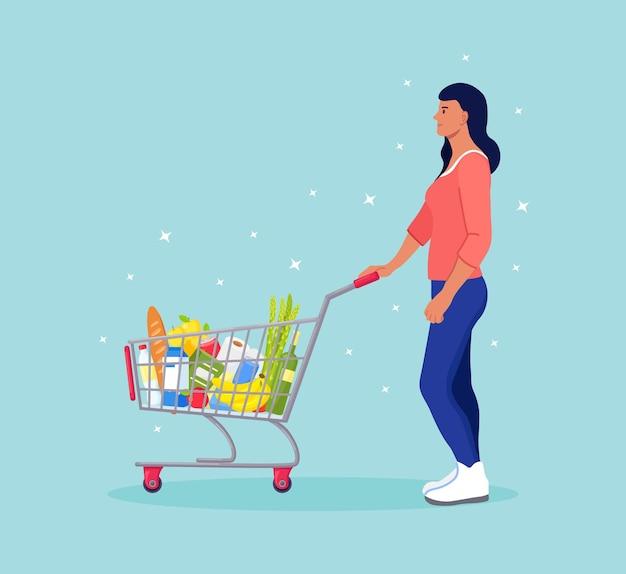 Vrouw duwen winkelwagen vol boodschappen in de supermarkt. er is een brood, flessen water, melk, fruit, groenten en andere producten in de mand