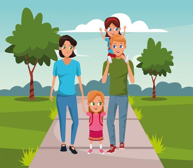 Vrouw en man die met leuke meisjes in het park lopen