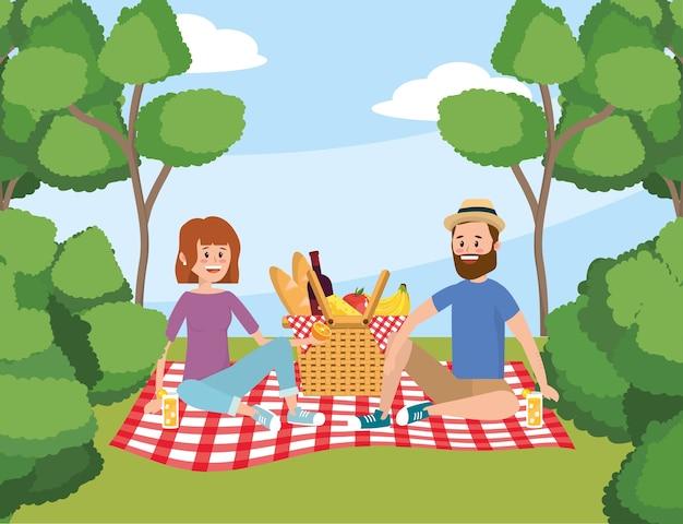 Vrouw en man met mandpicknick en bomen