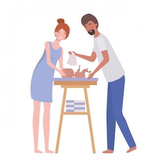 Vrouw en man met pasgeboren baby in luier het veranderen